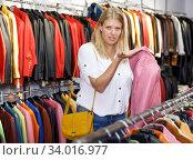 Купить «Displeased woman choosing leather clothes», фото № 34016977, снято 5 сентября 2018 г. (c) Яков Филимонов / Фотобанк Лори