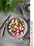 Купить «Radish, cucumber, kiwi, cheese and dill salad in a bowl on gray grunge concrete background. Seasonal Cooking, food styling.», фото № 34019169, снято 11 апреля 2019 г. (c) Nataliia Zhekova / Фотобанк Лори