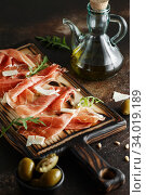 Traditional parma cured ham antipasto. Parma Ham and Parmesan Cheese. prosciutto, parmesan cheese, fresh arugula, olives and pine nuts on rustic wooden board. Meat platter board. Стоковое фото, фотограф Nataliia Zhekova / Фотобанк Лори