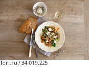 Купить «Mixed vegetable stir fry with mushrooms and cottage cream cheese. Tender mushroom stir fry served in a white plate with white wine and bread on the wooden table. Vegan food», фото № 34019225, снято 28 июня 2019 г. (c) Nataliia Zhekova / Фотобанк Лори