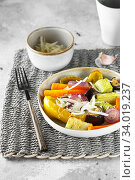 Купить «Mixed vegetable stir fry with parmesan cheese. Roasted vegetables mix on the plate with cutlery on the wicker serving mat, food above. Tender seasonal vegetables stir fry. Vegan food», фото № 34019237, снято 29 июля 2019 г. (c) Nataliia Zhekova / Фотобанк Лори