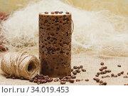 Beautiful Decorative Handmade candle with coffee beans on old sackcloth background. Стоковое фото, фотограф Nataliia Zhekova / Фотобанк Лори