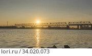 Timelapse of city river bank. Sun rays, blue sky and railway bridge over horizont. Summer sunset time with flat tiny waves water and motorised slider movement. Стоковое видео, видеограф Александр Маркин / Фотобанк Лори