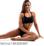 Купить «Slim sporty brunette wearing black top and briefs sitting on the floor isolated full-length view on white», фото № 34029601, снято 14 июля 2020 г. (c) easy Fotostock / Фотобанк Лори