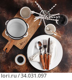 Купить «Crockery and cutlery on a dark background with copy space. White metal plates, bowls, cups and cutlery with wooden handles.», фото № 34031097, снято 12 ноября 2019 г. (c) Nataliia Zhekova / Фотобанк Лори