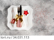 Купить «Christmas table place setting with square plate, cutlery with festive decorations gold ribbon, bauble red telephone box, star-shaped bowl with red sugar. Christmas Xmas New Year holiday backdrop», фото № 34031113, снято 12 ноября 2019 г. (c) Nataliia Zhekova / Фотобанк Лори