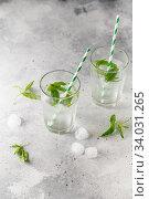 Купить «glasses of cold water with fresh mint leaves and ice cubes on grey concrete background», фото № 34031265, снято 4 июня 2019 г. (c) Nataliia Zhekova / Фотобанк Лори