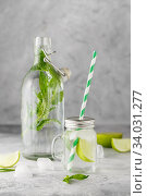 Glass Bottle and lemonade jar with cold lemonade with fresh mint leaves and lime with ice cubes on grey concrete background. Стоковое фото, фотограф Nataliia Zhekova / Фотобанк Лори