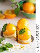 Купить «Mousse dessert with orange zest and mint in the shape of an orange fruit», фото № 34031537, снято 4 февраля 2019 г. (c) Nataliia Zhekova / Фотобанк Лори