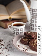 Купить «Still life composition of chocolate cookies on the plate, coffee cup, coffee pot and books. Food photo», фото № 34031541, снято 5 февраля 2019 г. (c) Nataliia Zhekova / Фотобанк Лори