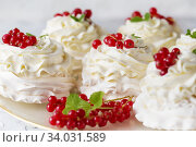 Купить «Pavlova cakes with cream and fresh summer berries. Close up of Pavlova dessert with forest fruit and mint. Food photo», фото № 34031589, снято 18 февраля 2019 г. (c) Nataliia Zhekova / Фотобанк Лори