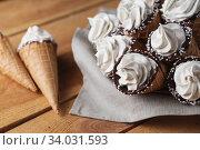 A lot of ice cream cones on wooden table. Soft ice creams or frozen custard in cones. Waffle marshmallow. Стоковое фото, фотограф Nataliia Zhekova / Фотобанк Лори