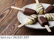 Milk chocolate popsicles on a stick. Ice cream popsicles covered with white and dark chocolate on the plate on wooden background. Space for text. Chocolate ice cream bars, nuts. Стоковое фото, фотограф Nataliia Zhekova / Фотобанк Лори