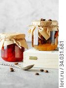 Купить «two jars of fruit homemade jam. pear marmalade with coffee beans and Jar of blood orange jam», фото № 34031681, снято 23 апреля 2019 г. (c) Nataliia Zhekova / Фотобанк Лори