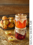 Apricot jam on a wooden rustic background. Two jars of fruit homemade marmalade. Glass jars with different kinds of fruits. Стоковое фото, фотограф Nataliia Zhekova / Фотобанк Лори