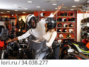 Couple sitting together on new motorcycle in store and having fun. Стоковое фото, фотограф Яков Филимонов / Фотобанк Лори
