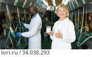 Farm female milkmaids with fresh milk standing near cow milking machines. Стоковое фото, фотограф Яков Филимонов / Фотобанк Лори
