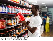 Купить «Athletic African looking for necessary food supplements», фото № 34038321, снято 13 июля 2020 г. (c) Яков Филимонов / Фотобанк Лори