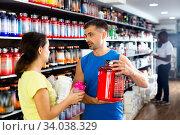 Confident athletically built man recommending sports supplements to female client at sports nutrition store. Стоковое фото, фотограф Яков Филимонов / Фотобанк Лори
