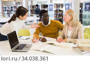 Female tutor helping students preparing for exam in library. Стоковое фото, фотограф Яков Филимонов / Фотобанк Лори