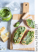 Toasts with traditional Italian basil pesto sauce on a light stone table. Green pesto with pine nuts and parmesan. Стоковое фото, фотограф Nataliia Zhekova / Фотобанк Лори