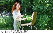 Young redhead woman draws a picture in the open air in the forest. Стоковое видео, видеограф Алексей Кузнецов / Фотобанк Лори