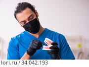 Купить «Young male dentist working in the clinic», фото № 34042193, снято 1 февраля 2020 г. (c) Elnur / Фотобанк Лори