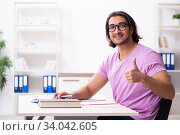 Купить «Young male student preparing for exams at classroom», фото № 34042605, снято 29 ноября 2019 г. (c) Elnur / Фотобанк Лори