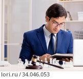 Купить «Young lawyer playing chess to train his court strategy and tacti», фото № 34046053, снято 31 июля 2018 г. (c) Elnur / Фотобанк Лори