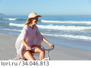 Купить «Caucasian woman spending time seaside and riding a bike», фото № 34046813, снято 25 февраля 2020 г. (c) Wavebreak Media / Фотобанк Лори