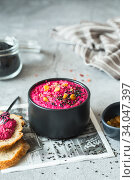 Beetroot dipping sauce in the black bowl decorated with sesame seeds and raisins. Vegan recipes, plant-based dishes. Green living. Стоковое фото, фотограф Nataliia Zhekova / Фотобанк Лори