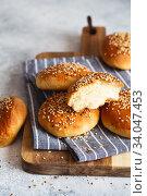 Купить «bun buns with sesame seeds on a wooden board.», фото № 34047453, снято 10 апреля 2020 г. (c) Nataliia Zhekova / Фотобанк Лори