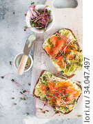 Toast with avocado cream and smoked salmon on the white wooden board. Smoked salmon, cream cheese and pesto toast sandwiches with radish microgreens sprouts. Стоковое фото, фотограф Nataliia Zhekova / Фотобанк Лори