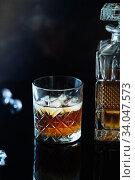 Glass of whiskey or bourbon with ice on black stone table. Glass of whiskey with ice and a square decanter. Glass of scotch whiskey. Стоковое фото, фотограф Nataliia Zhekova / Фотобанк Лори