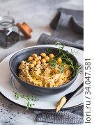 Купить «Chickpeas hummus in the black bowl decorated with sesame seeds and chickpeas greens. Vegan recipes, plant-based dishes. Green living concept. Organic food. Vegetarian», фото № 34047581, снято 2 марта 2020 г. (c) Nataliia Zhekova / Фотобанк Лори