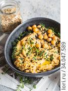 Купить «Chickpeas hummus in the black bowl decorated with sesame seeds and chickpeas greens. Vegan recipes, plant-based dishes. Green living concept. Organic food. Vegetarian», фото № 34047589, снято 2 марта 2020 г. (c) Nataliia Zhekova / Фотобанк Лори