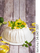 Купить «Pavlova cake with cream and fresh fruits - lime, carambola and green mint leaves. Close up of Pavlova dessert with yellow and green fruits. Food photography», фото № 34047597, снято 25 февраля 2020 г. (c) Nataliia Zhekova / Фотобанк Лори