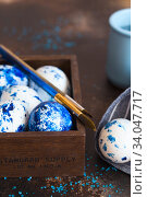 Купить «Dyed Easter eggs. Сlassic blue Easter eggs on the brown background. Blue speckled easter eggs with paint and brushes. Decorating eggs, preparing for Easter», фото № 34047717, снято 27 февраля 2020 г. (c) Nataliia Zhekova / Фотобанк Лори
