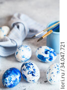 Купить «Dyed Easter eggs. Сlassic blue Easter eggs on the grey background. Blue speckled easter eggs with paint and brushes. Decorating eggs, preparing for Easter», фото № 34047721, снято 27 февраля 2020 г. (c) Nataliia Zhekova / Фотобанк Лори