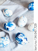 Купить «Dyed Easter eggs. Сlassic blue Easter eggs on the grey background. Blue speckled easter eggs with paint and brushes. Decorating eggs, preparing for Easter», фото № 34047729, снято 27 февраля 2020 г. (c) Nataliia Zhekova / Фотобанк Лори