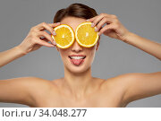 Купить «beautiful woman making eye mask of orange slices», фото № 34048277, снято 30 ноября 2019 г. (c) Syda Productions / Фотобанк Лори
