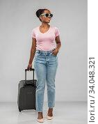 Купить «happy african woman in sunglasses with travel bag», фото № 34048321, снято 26 января 2020 г. (c) Syda Productions / Фотобанк Лори
