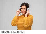 Купить «happy woman in headphones listening to music», фото № 34048421, снято 20 марта 2020 г. (c) Syda Productions / Фотобанк Лори
