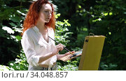 Middle aged redhead woman draws a picture in the open air in the forest. Стоковое видео, видеограф Алексей Кузнецов / Фотобанк Лори