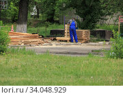 Profession of carpenter. Carpentry with boards in the open air in summer and spring, among the greenery. Стоковое фото, фотограф irisff / Фотобанк Лори