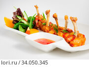 Fried chilli chicken wings with vegetable salad and hot sauce. Стоковое фото, фотограф Zoonar.com/Serghei Starus / easy Fotostock / Фотобанк Лори