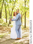 Купить «Just married loving hipster couple in wedding dress and suit in the park. Happy bride and groom walking running and dancing. Romantic Married young family.», фото № 34053613, снято 5 октября 2018 г. (c) Nataliia Zhekova / Фотобанк Лори