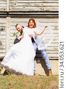 Купить «Just married loving hipster couple in wedding dress and suit posing in front of an old wooden house. Happy bride and groom walking running and dancing. Romantic Married young family», фото № 34053621, снято 5 октября 2018 г. (c) Nataliia Zhekova / Фотобанк Лори