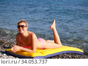 Girl at the sea. Attractive blonde-haired woman sunbathes recline on inflatable swimming mattress on pebble beach. Стоковое фото, фотограф Константин Сиятский / Фотобанк Лори