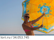 Smiling woman in sunglasses against a blue sky holds a large parasol in his hands. Стоковое фото, фотограф Константин Сиятский / Фотобанк Лори